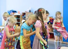Girls tie aprons each other in kindergarten. Preschool girls tie aprons each other in kindergarten Stock Photo