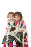 Girls in tinsel. Portrait of sisters wrapped up with Christmas tree tinsel Royalty Free Stock Images