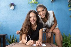 The girls about to write smile with joy. Smiling girls sitting in a wooden chair, look and smile while one keeps a pen in his hand and a notebook Stock Photography