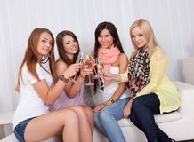 Girls toasting with champagne. Group of attractive stylish girls with lovely smiles standing close together toasting with champagne Royalty Free Stock Images