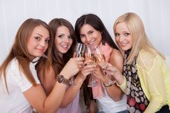 Girls toasting with champagne. Group of attractive stylish girls with lovely smiles standing close together toasting with champagne Royalty Free Stock Photography