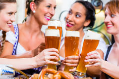 Girls toasting with wheat beer in Bavarian pub. In front of pretzel stock photo