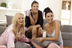 Girls watching tv at home. Girls together at home, watching tv in pyjamas, smiling happy Royalty Free Stock Image