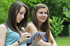 Girls with touchpad. Two young girls on bench using a tablet computer outdoor in park Royalty Free Stock Photography