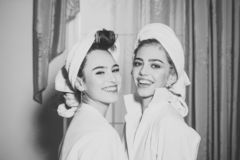 Girls with towels on heads wear bathrobe with curtains. On background. ladies with smiling happy faces after wellness and spa procedures, or morning shower stock photo