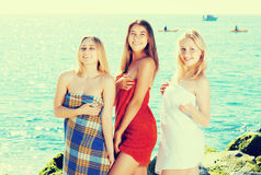 Girls in towels standing on beach stock photo