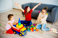 Girls with toy car. Three girls playing with a toy car Royalty Free Stock Image