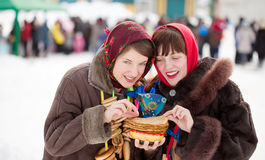 Girls in traditional  clothes tasting pancake. During  Shrovetide Royalty Free Stock Images