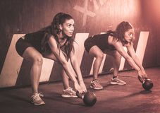 Crossfitters training hard daily wod kettlebells royalty free stock image