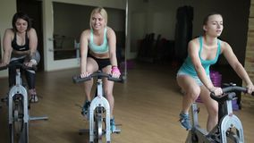 Girls training on exercise bikes in the gym stock footage