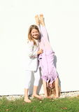 Girls training handstand. Exercising barefoot girl with long hair dressed in white clothes is  trainging handstand while second kid is holding her Royalty Free Stock Photos