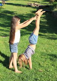 Girls training handstand. Exercising barefoot girl with long hair is trainging handstand while second one is catching her Royalty Free Stock Photo