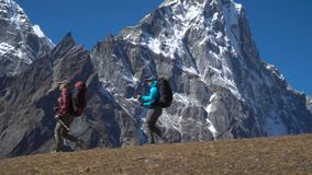 Girls travel in the Himalayas. Two girls with backpacks travel in the Himalayas. Beautiful view of the snowy peaks. The concept of travel and adventure stock footage