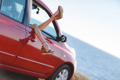 Girls - travelers relaxing in the car. Day dreaming in car. Close-up of young woman holding legs out of the window while sitting inside the car. female legs royalty free stock photo