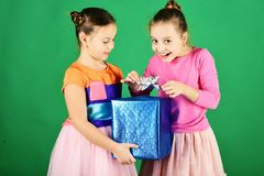 Girls with tricky faces pose with present on green background. Birthday surprise concept. Sisters with wrapped blue gift box for holiday take silver bow off royalty free stock photography