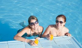 Girls in tropical pool with orange juice Stock Image