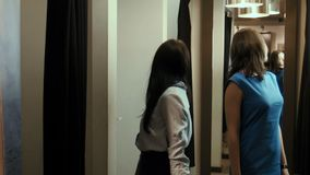 Girls try on dresses in a fitting room stock video