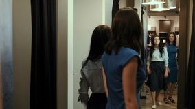 Girls try on dresses in a fitting room stock video footage