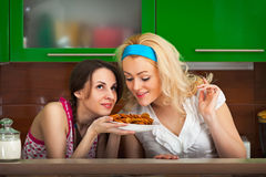 Girls try the freshly cooked homemade cookies Royalty Free Stock Photography