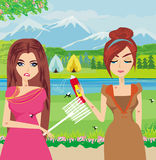 Girls trying to kill a mosquito Royalty Free Stock Images