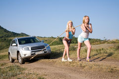 Girls tugging car. Two young beauty girl tugging car on the solitary road stock image