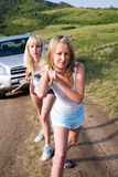 Girls tugging car. Two young beauty girl tugging car on the solitary road Royalty Free Stock Photos