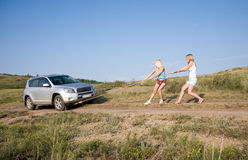 Girls tugging car. Two young beauty girl tugging car on the solitary road royalty free stock photo