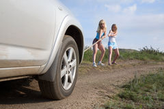 Girls tugging car. Two young beauty girl tugging car on the solitary road stock photos