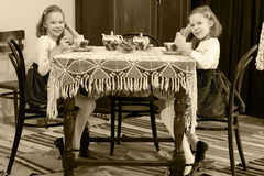 Girls Twins drinking tea at an antique table with a lace tablecl Royalty Free Stock Photos