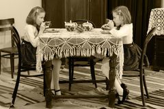Girls Twins drinking tea at an antique table with a lace tablecl Royalty Free Stock Images