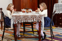Girls Twins drinking tea at an antique table with a lace tablecl Stock Photography