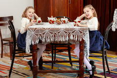 Girls Twins drinking tea at an antique table with a lace tablecl Royalty Free Stock Photography
