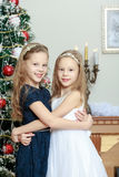 Girls twins with gifts e Christmas tree. Adorable little twin girls hugging each other near the Christmas tree Stock Images
