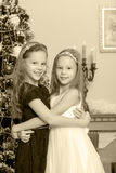 Girls twins with gifts e Christmas tree. Adorable little twin girls hugging each other near the Christmas tree.Black-and-white photo. Retro style Royalty Free Stock Photo