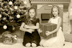 Girls twins with gifts e Christmas tree. Royalty Free Stock Image