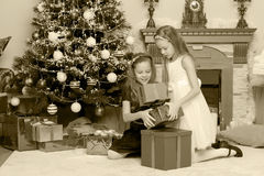 Girls twins with gifts e Christmas tree. Stock Photo