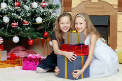 Girls twins with gifts e Christmas tree. Royalty Free Stock Photography