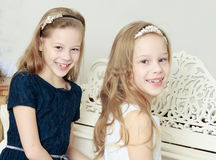 Girls Twins playing the piano. Adorable little twin girls playing on a white piano near the Christmas tree Stock Photo