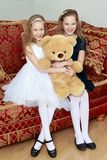 Girls twins with a Teddy bear. Two adorable little twin girls sitting on sofa hugging a big Teddy bear Stock Photography