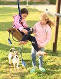 Girls twisting on swing. Two smiling kids - barefoot girls playing and twisting on swing with dog behind Royalty Free Stock Image