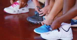 Girls tying shoe laces in basketball court stock video footage
