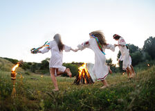 Girls in Ukrainian national shirts dancing around a campfire. Midsumer