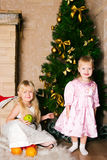The girls under the Christmas fir-tree Stock Image