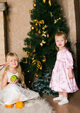 The girls under the Christmas fir-tree Royalty Free Stock Image