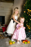 The girls under the Christmas fir-tree Royalty Free Stock Photography
