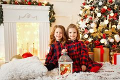 Girls under Christmas tree. Two cute little girls in checkered dresses sitting under Christmas tree and looking at camera stock photography