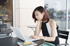 Girls use computers. Asian girls use tablets.In a street cafe Stock Photo