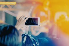 Girls use smartphones to take pictures at concerts royalty free stock image