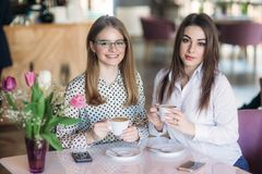 Girls use their break from work to drink coffee and chat. Caffe cappuccino. Girls use their break from work to drink coffee and chat. Caffe cappuccino royalty free stock photo