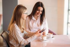 Girls use their break from work to drink coffee and chat. Caffe cappuccino. Girls use their break from work to drink coffee and chat. Caffe cappuccino stock photo